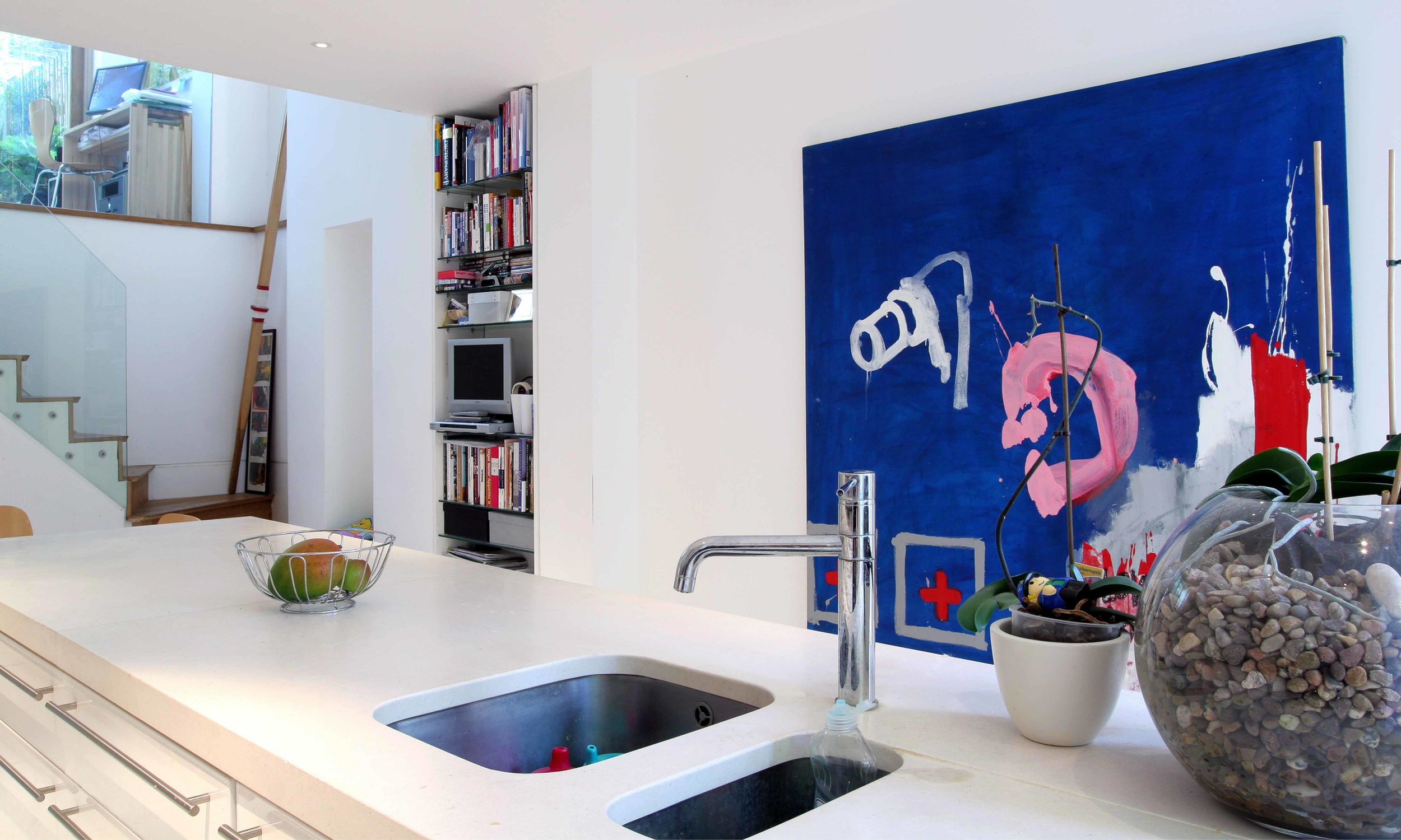 The new kitchen in the basement of the property. The glass __ to the staircase brings additional light to allow the space be naturally light. Modern art hangs on the walls bringing colour to the space.
