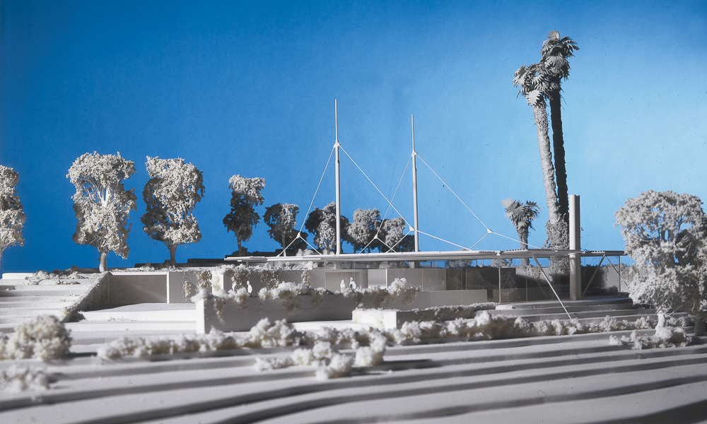A swimming pool and terrace sit beside the main building. The masts hold up the roof allowing a column-less structure with panoramic views of the surrounding landscape.