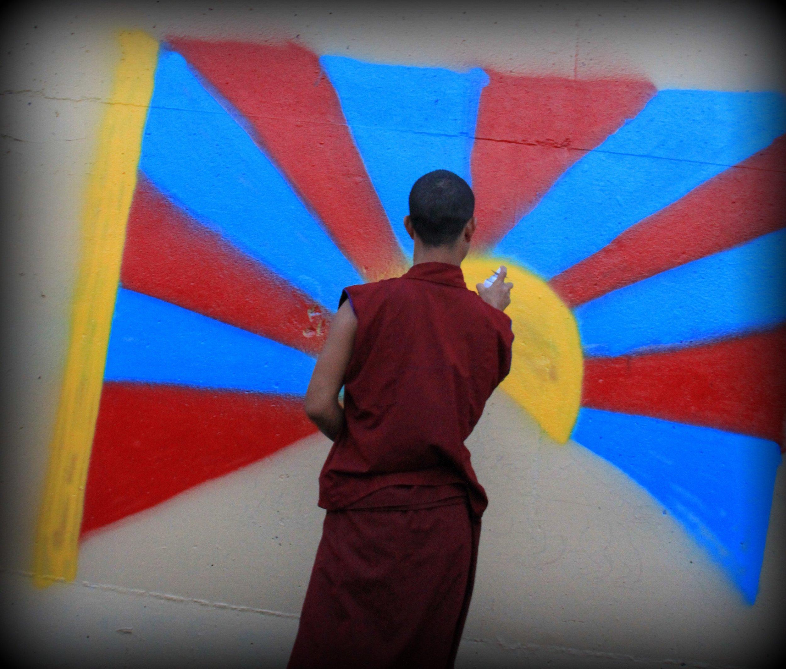 Tibetan Buddhist monk paints the Tibetan flag on the Kosciusko Graffiti Wall, 2014.  The Curator  .