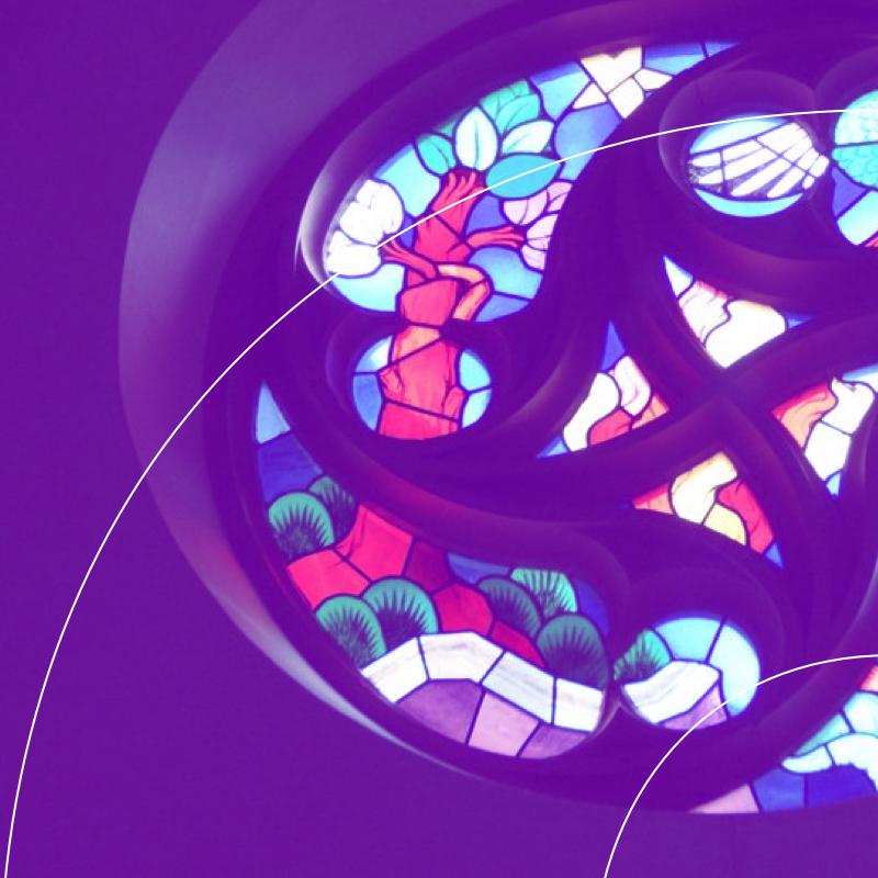 Kibeo Kirchenfenster Podcast. Das Licht bricht sich im Mosaik des Fensters, Die einzelnen Farben leuchten auf.