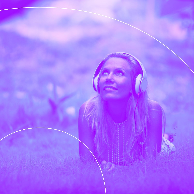Kibeo Gottesdienst Podcast. Eine junge Frau mit Kopfhörern liegt bäuchlings auf den Unterarmen abestützt auf einer Wiese, die Augen zum Himmel gerichtet und lächelt.