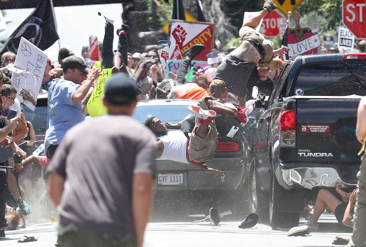 The black Challenger that would take the life of Heather Heyer narrowly misses law students Leanne Chia and Elizabeth Sines. Photo courtesy Daily Progress.