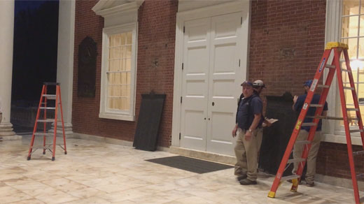 Workers pry Confederate plaques off the Rotunda's facade. Photo Courtesy Daily Progress.