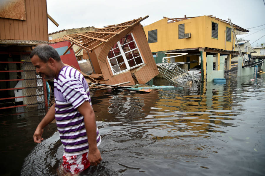 Puerto Rican resident wades through flooded street after Hurricane Maria. Photo courtesy of Hector Retamal/AFP/Getty Images.