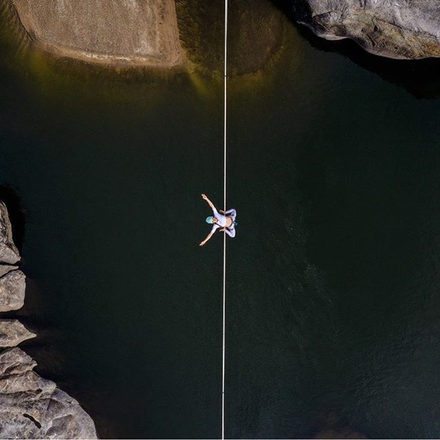 Working on editing the last episode of @projectflowmance where @lizasouras and I go to Utah and Highline with our monkey friends.  In the mean time here's a shot of Liz doing a double drop knee over a river in Cali with our new drone❤️ . . #highlining #slacklife #slackline #slacker #california #river
