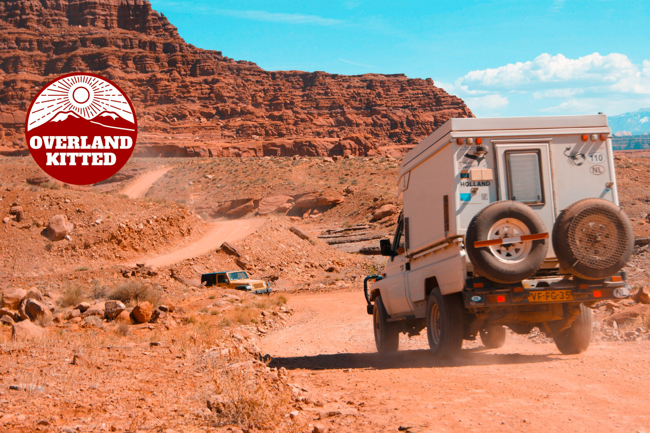 An early model Toyota Hilux passing a late model Jeep JK on the trail during a multi-continental overland adventure.