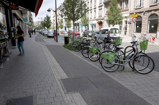 [Image:The bike lane is integrated in the sidewalk and the zone adjacent to the street is used for parallel car parking, bike racks, street furniture, trees, and bulb-outs.]