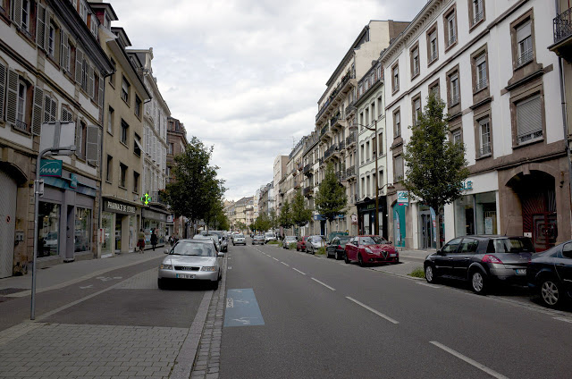 [Image:Parallel parking along Rue du Faubourg de Pierre is slightly raised and uses pavers instead of asphalt, which visually narrows the street.]