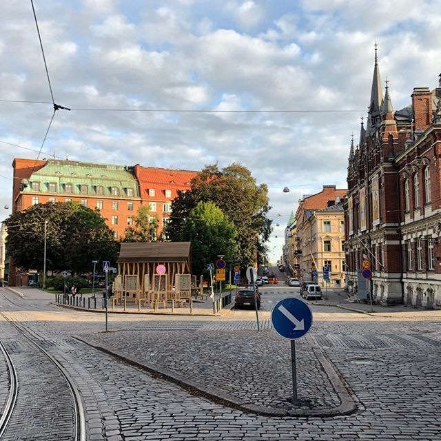 This cobblestone streetscape is in Helsinki. The treatment and texture of the street and island invites people to walk. The space for tracks and vehicular streets is made as narrow as possible. The buildings on the edge of the streets are formal, have significant mass, and help to enclose the park. Art is displayed in the park.