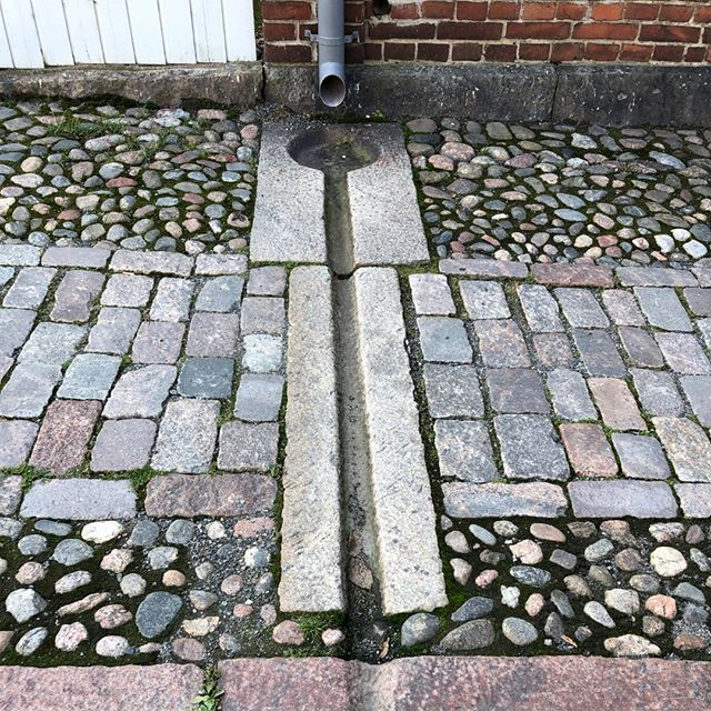 The paved treatment reveals careful attention to the sidewalk and all its functions, with a curb, walking path, and a drainage basin. All made with a different texture, a colorful selection of stones, and over a century ago in Turku Finland.