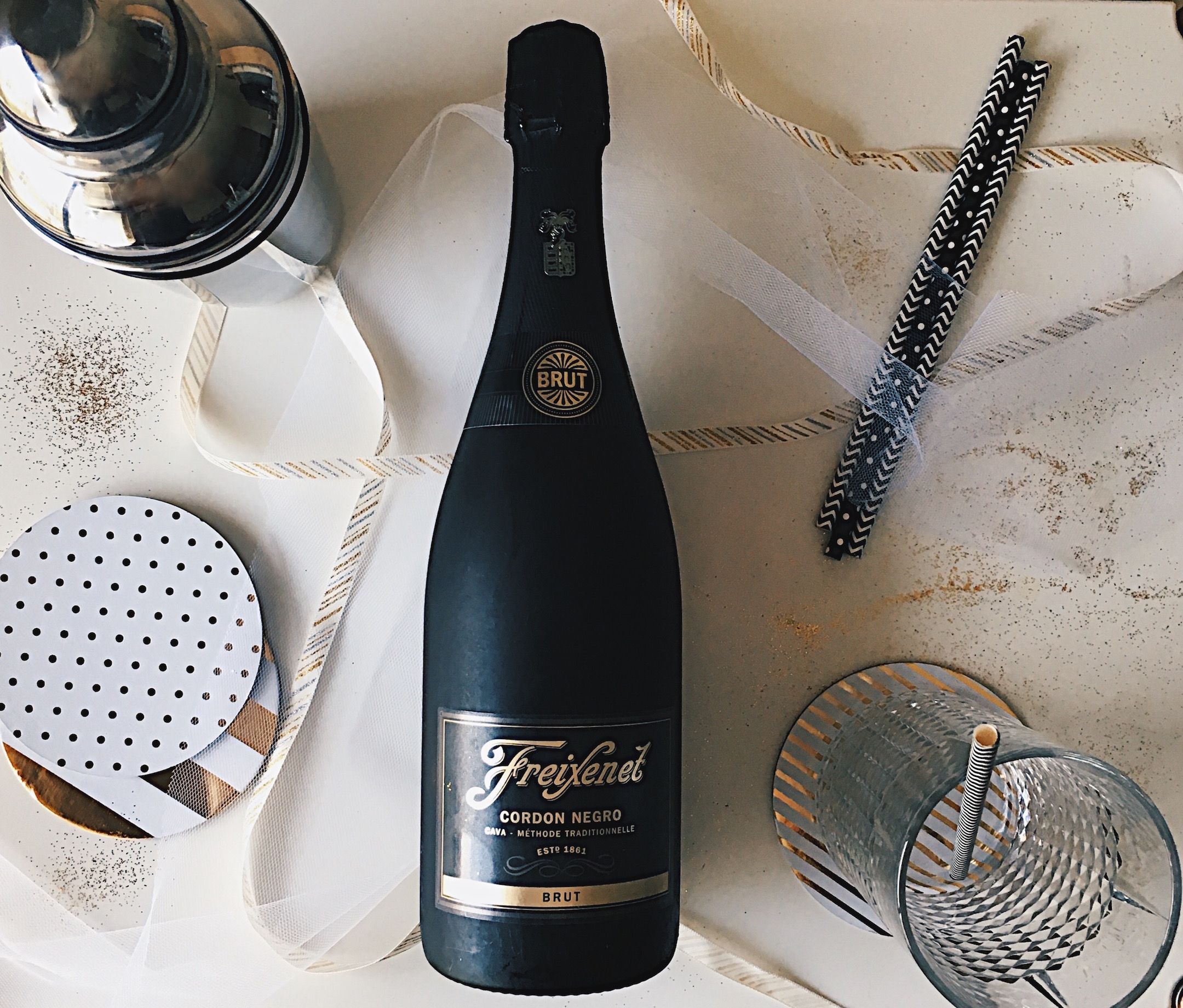 Freixenet Cordon Negro Brut Champagne/ Gold glitter table setting/ Black and White Paper straws/ silver shaker