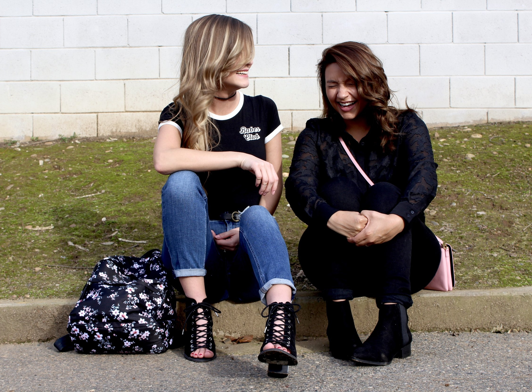 Babes Club Tee, denim pants, with open toed lace up shoes. All black outfits with a pop of pink. Two friends sitting curbside