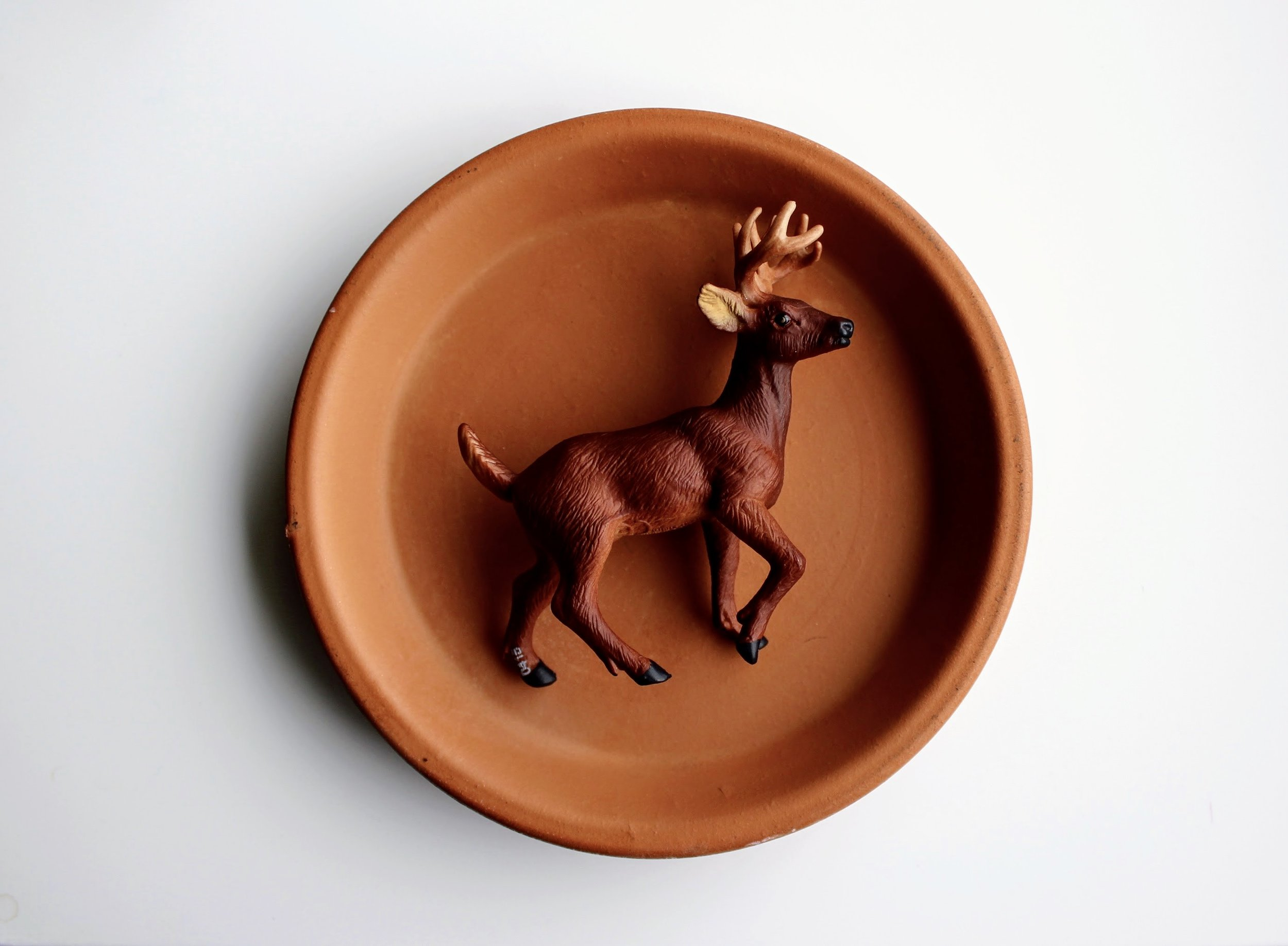 Planter Saucer and Plastic Deer Figurine