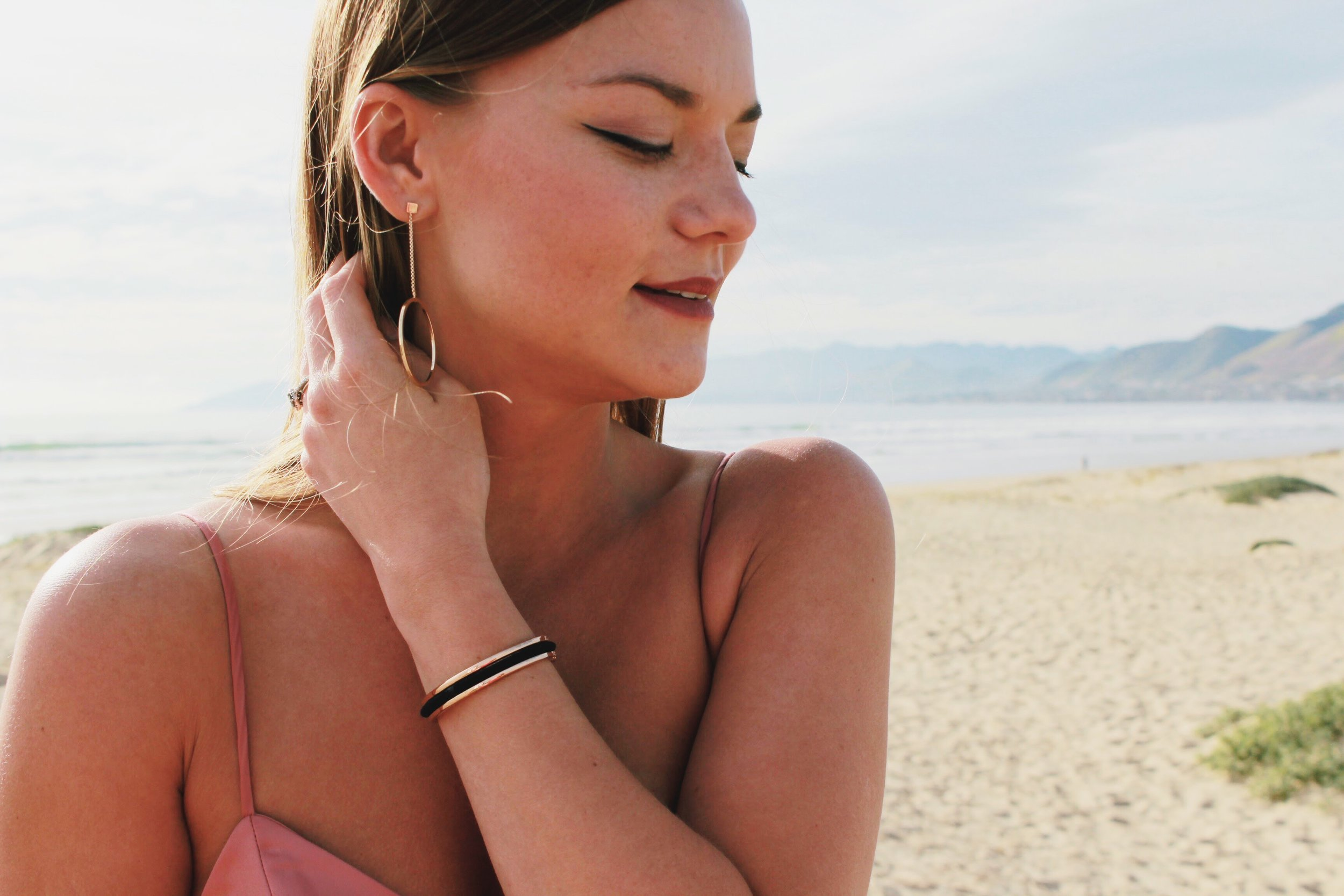 Gold Dangle Earrings with Pink Satin Dress and Gold Floral HairTie Bracelet with a beach Background.