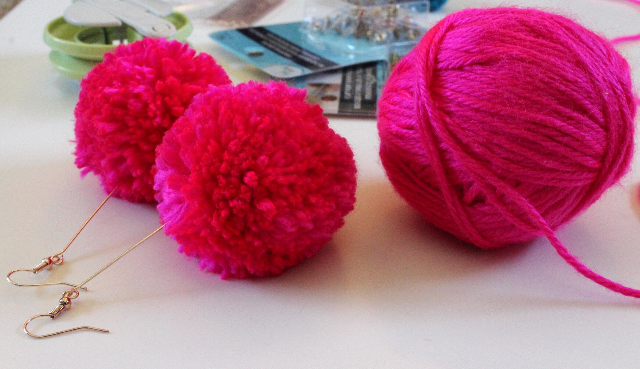 Hot Pink Pom Pom Dangle Earrings and Ball of Yarn.