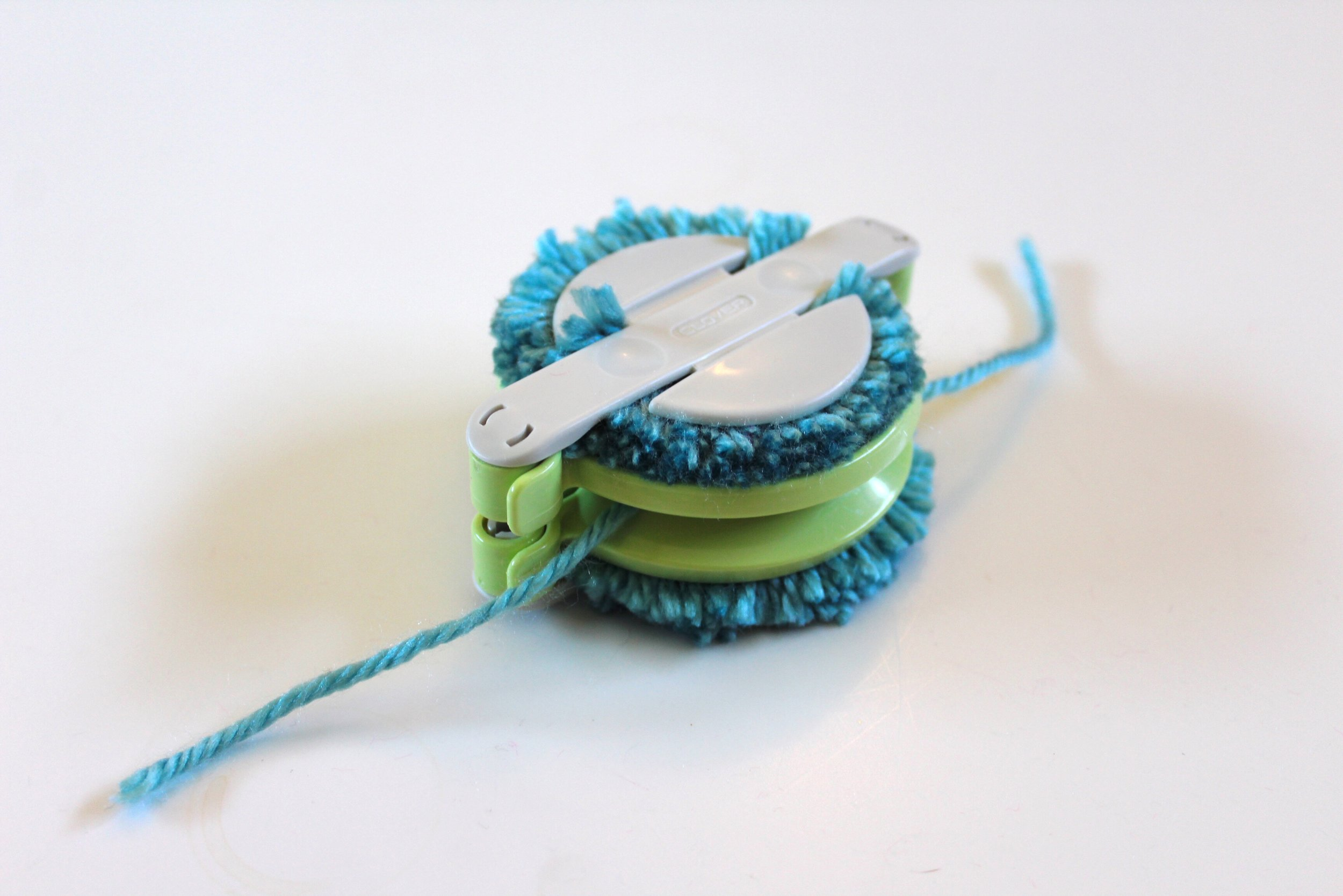 Clover Pom Pom Maker. Yarn has been cut and yarn tied to keep the pom pom together.