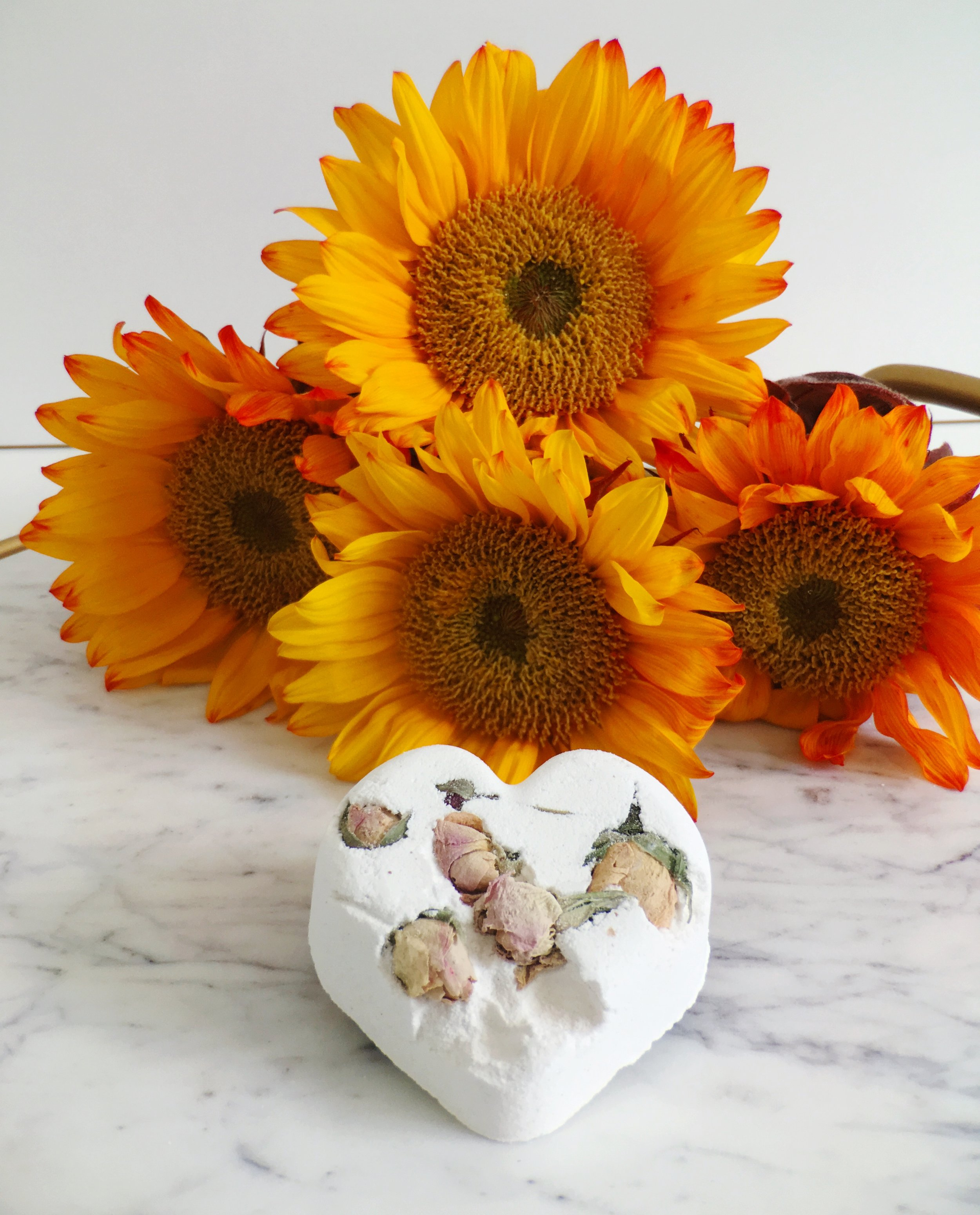 Sun Flowers on a Marble Table Top with a Lush Cosmetics Bath Bomb. Titsy Totsy includes dried roses