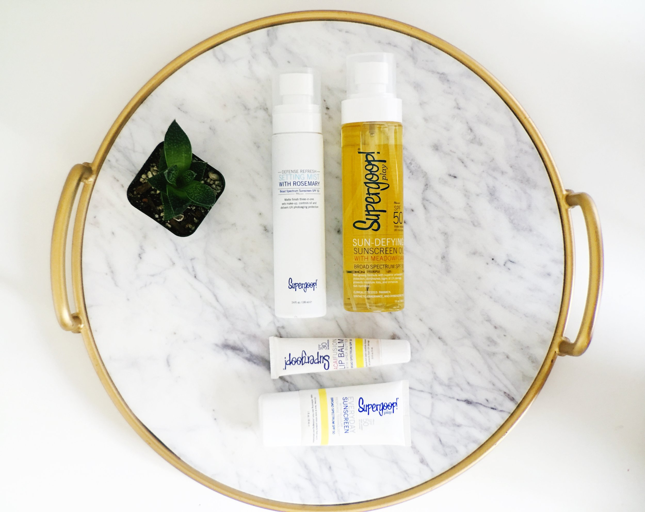 SuperGoop Sun Block products including Sunscreen oil, setting mist spray, lip balm and face sunscreen.