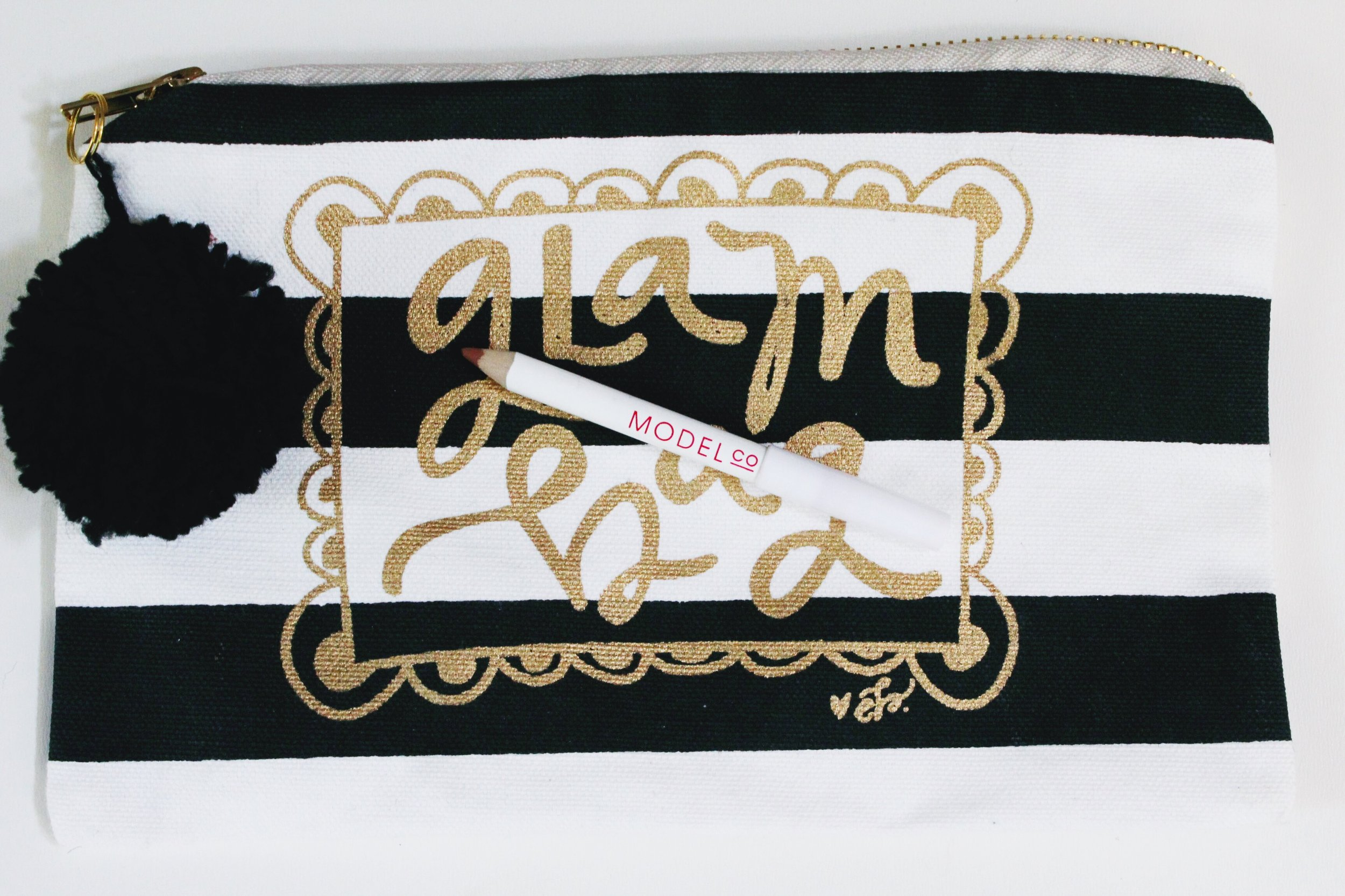 Black and White Striped Glam Bag with a zipper Pom pom and Model Co Lip enhancing lip liner