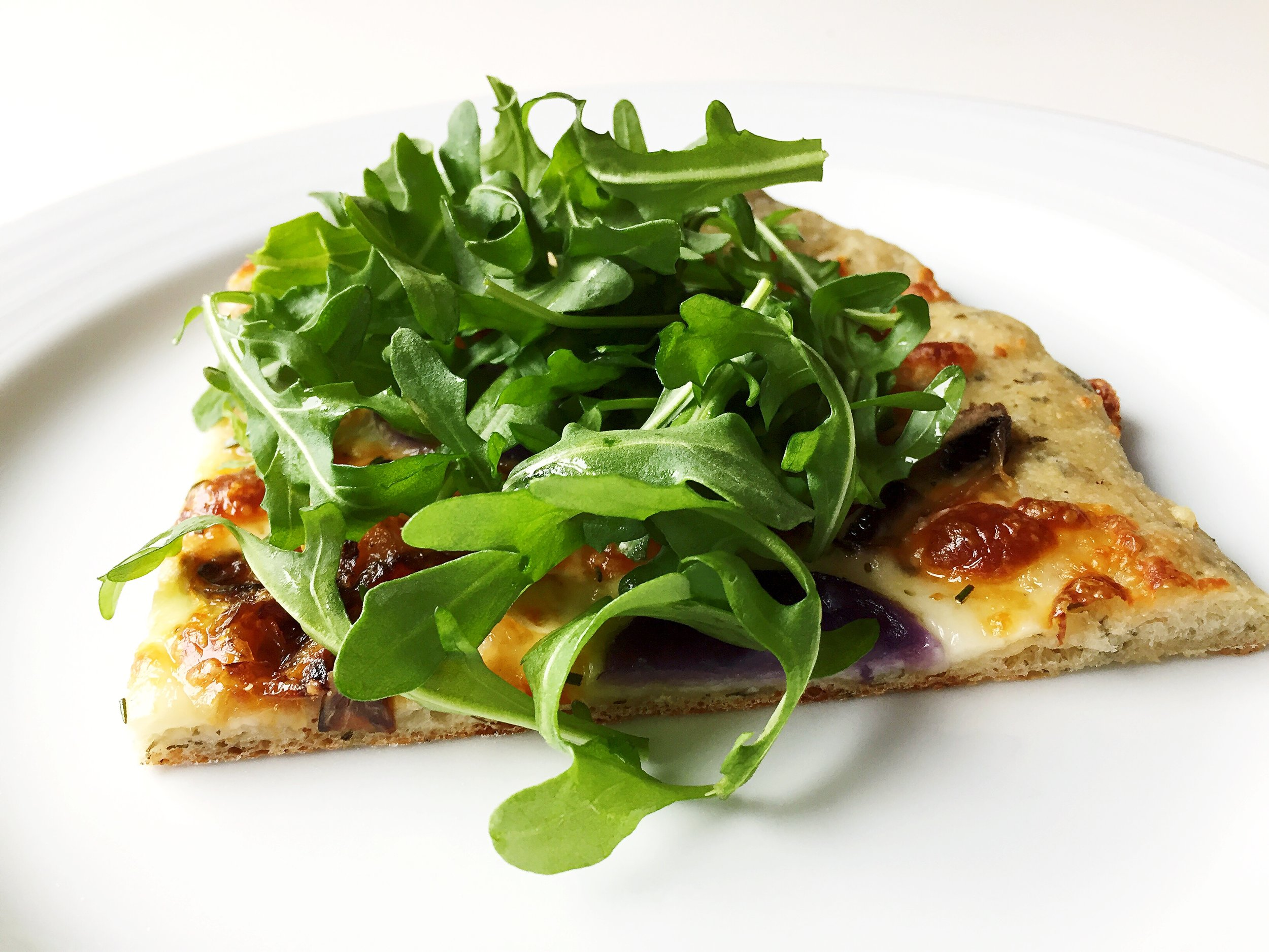 Purple Potato Pizza topped with arugula