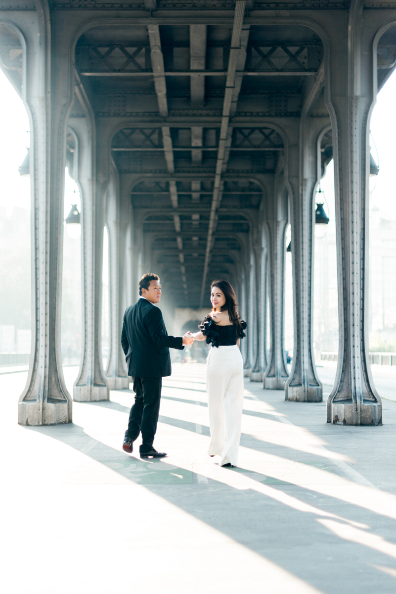 Photographer in paris - Walking together under a bridge in Paris during a couple photo shoot