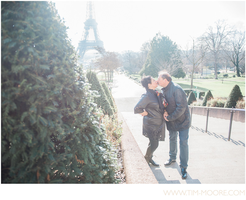 A very cute couple kissing in front of the Eiffel Tower to celebrate their eternal love