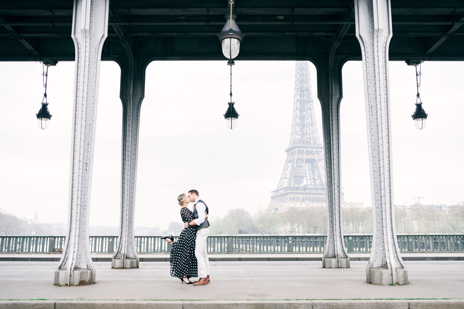 Paris Photographer - A couple kissing in front of the Eiffel Tower in Paris by Tim Moore