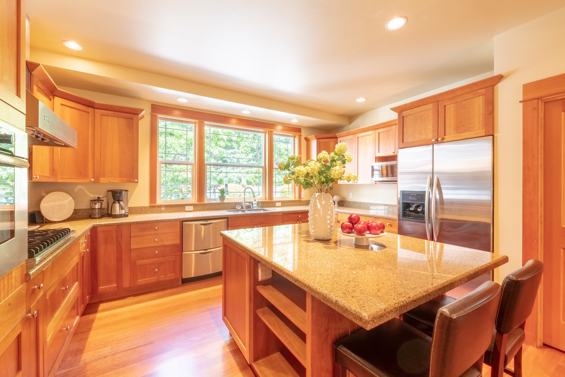 The kitchen includes a 6-burner Wolf gas range, Bosch oven, Fisher & Paykel Dish Drawer dishwasher, large counter depth fridge and microwave.