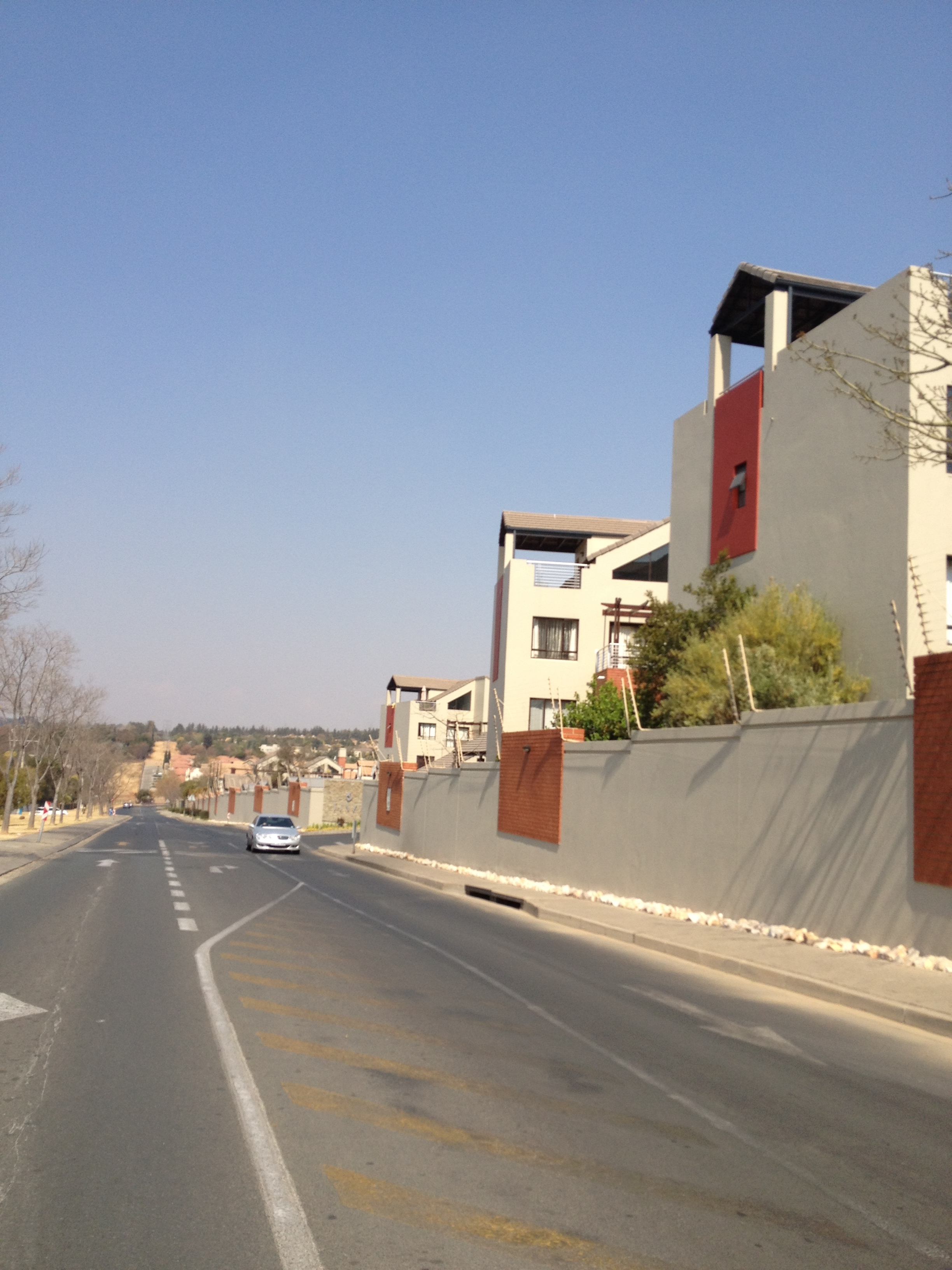 A typically suburban scene in newly-developed areas of Johannesburg, where public space functions merely as a road arterial connecting enclosed townhouse/condominium developments.