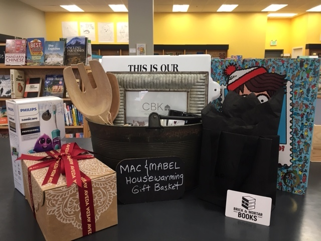 A selection of prizes, including a housewarming basket from Mac & Mabel, a set from Redmond Signature Dentistry, a gift box from Aveda, gift cards and Waldo books from Brick & Mortar Books.