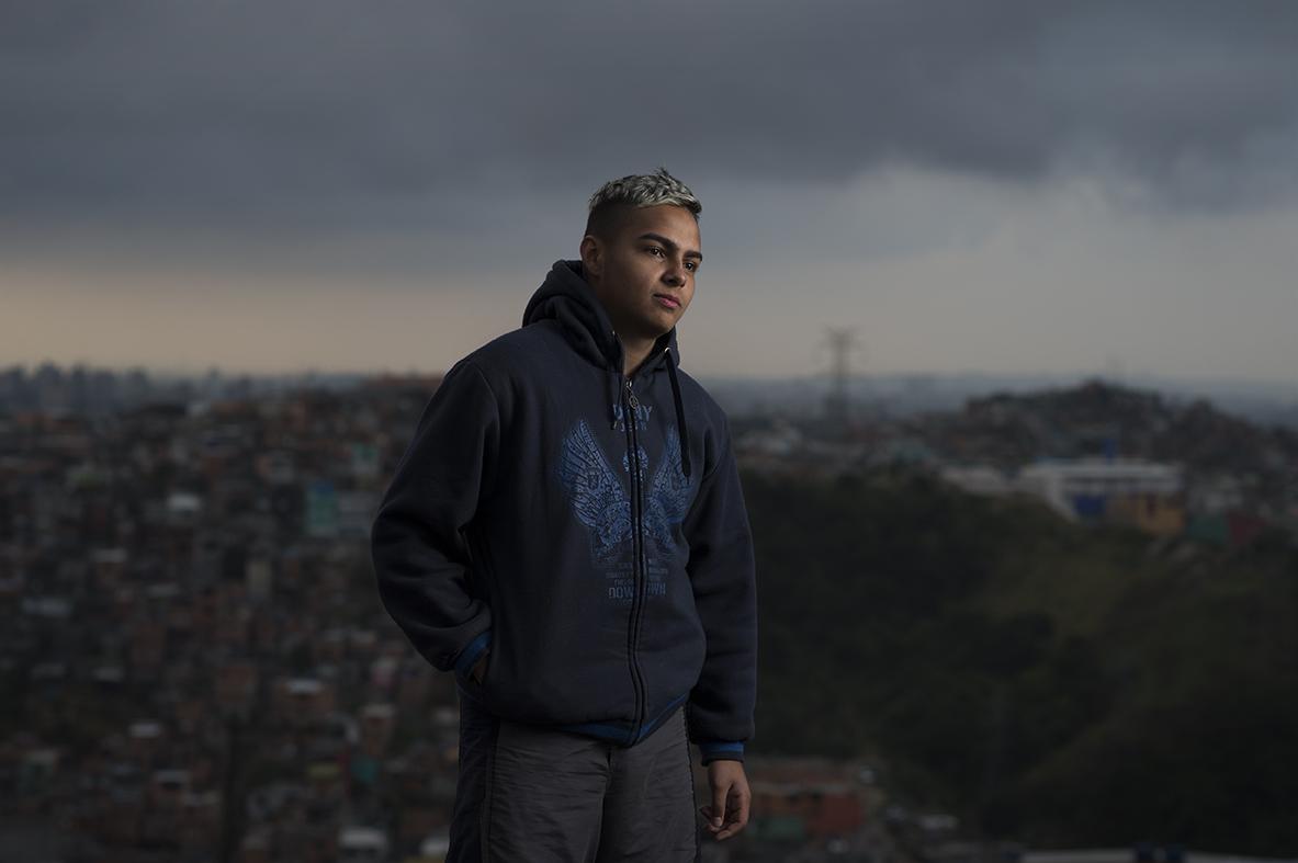 Wellington Gomes, 16, poses for the camera behind his home in São Bernardo favela, São Paulo, on August 12, 2016.