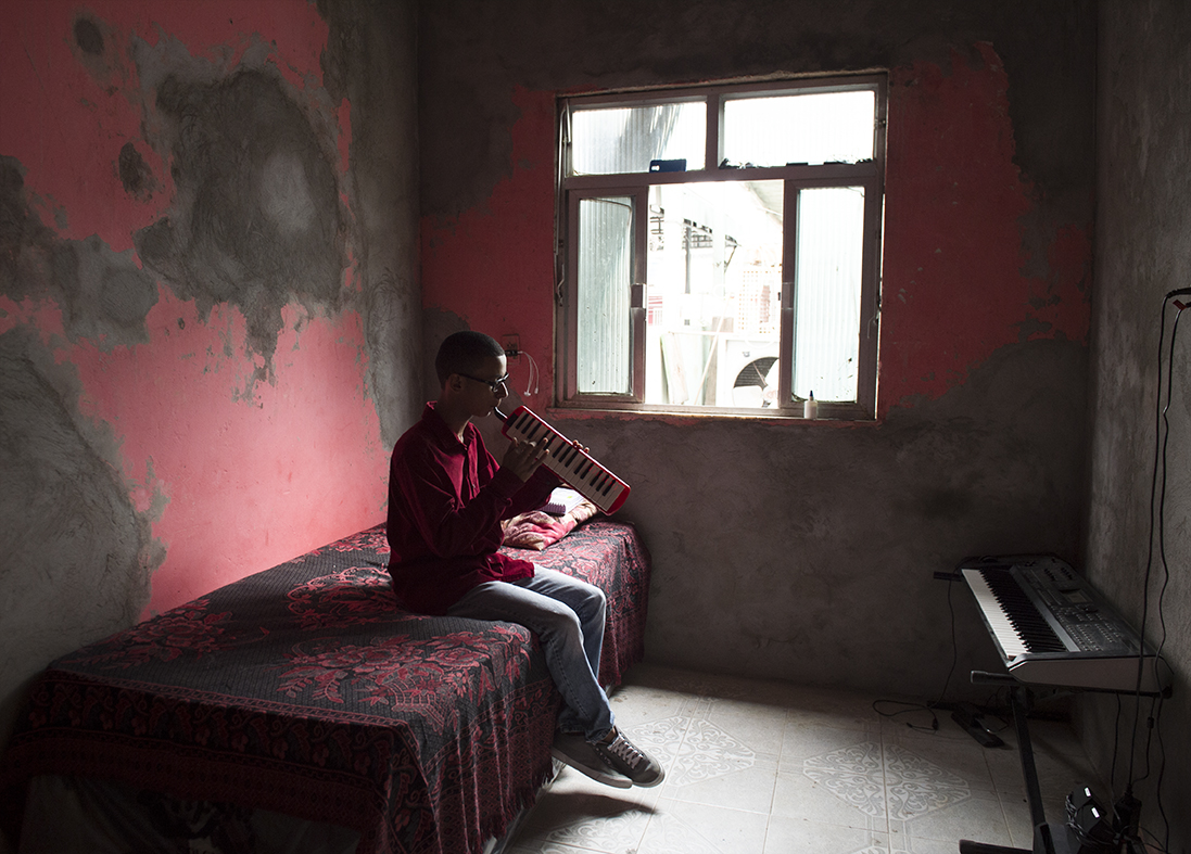 Lucas Freitas, 16, shows where hepractices pianica in his bedroom at Campos Eliseos, a poor neighbourhood in northern Rio de Janeiro on August 20, 2016.