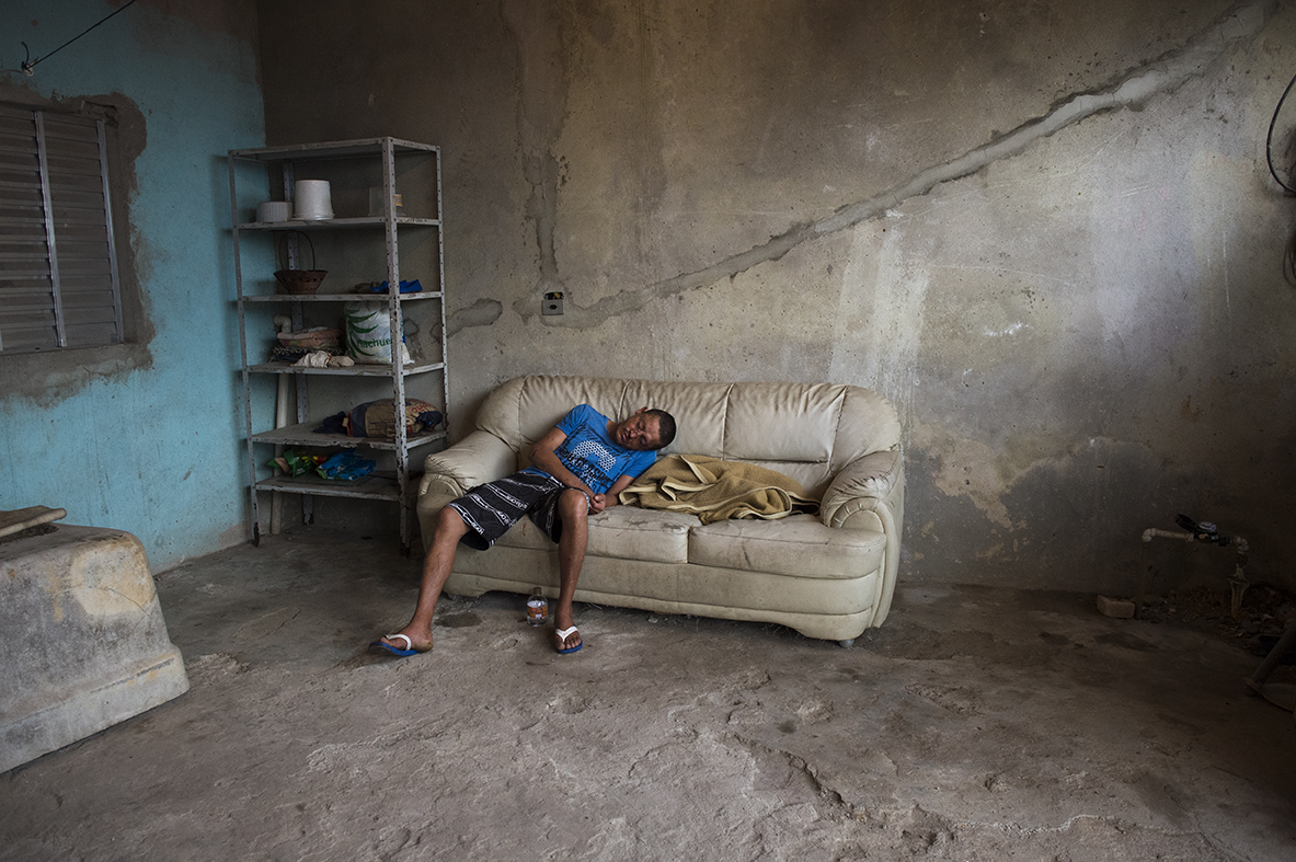 An unnamed alcoholic sleeps after passing out in his home in São Bernardo favela, São Paulo, on August 9, 2016. His mother, unseen, explains that his facial scars and bruises were as a result of falling in the shower while drunk.