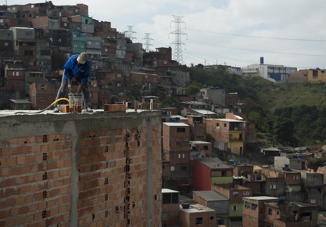 Valdinei lays bricks on a three-storey home in Santo André favela, São Paulo, August 12, 2016.