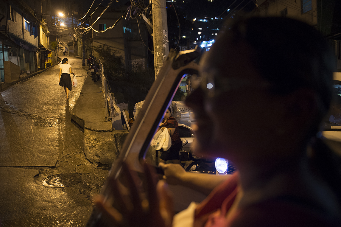 A resident holds a car door which has fallen off as she was getting out of the car in Vidigal favela on August 18, 2016.