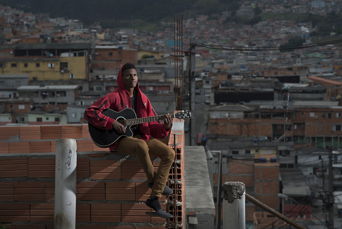 """Matheus Gadelha, a 19-year old unemployed resident of Santo Andre favela, Sao Paulo, Brazil, poses for the camera as he practices a guitar by his home, on August 12, 2016. Matheus dreams to become a professional musician. The teen has never met his father and says """"I'm very happy without him, my mother is everything to me."""""""