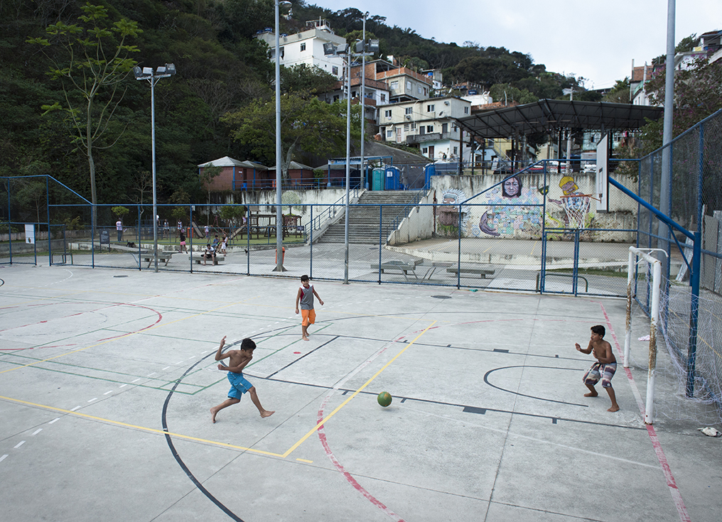 Footballers have a kick-about inside Vidigial favela in Rio on August 18, 2016.