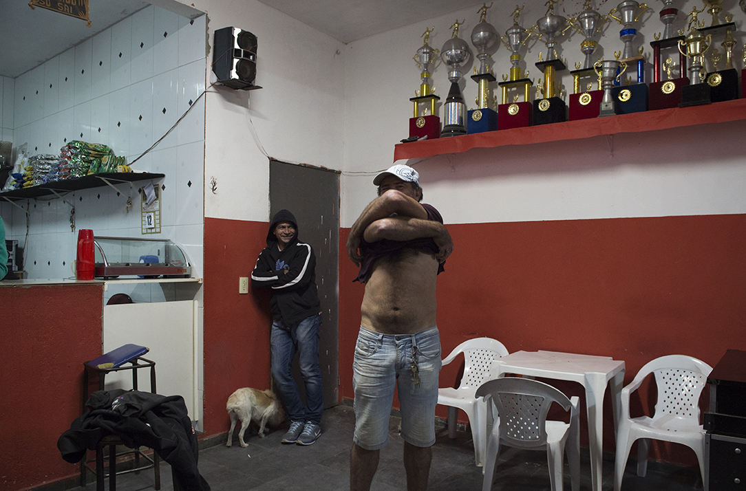 A drunken man takes off his top at a bar in Santo Andre favela, Sao Paulo, Brazil