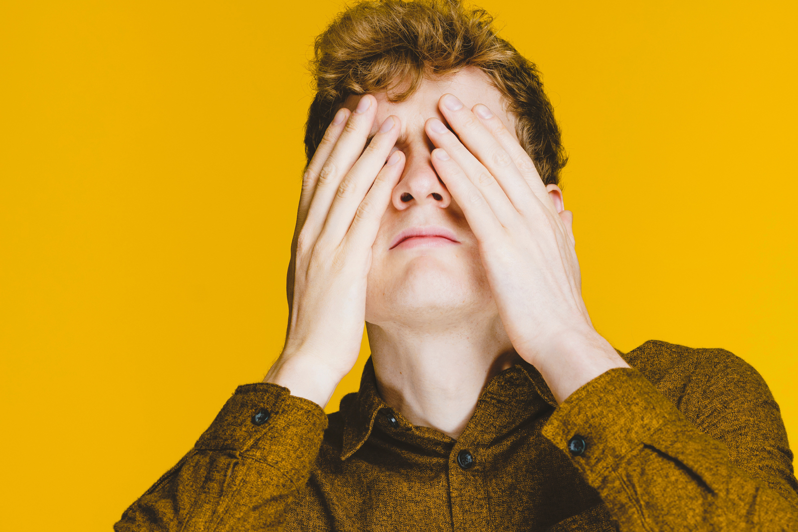 A photo of James Acaster hiding his face with his two hands