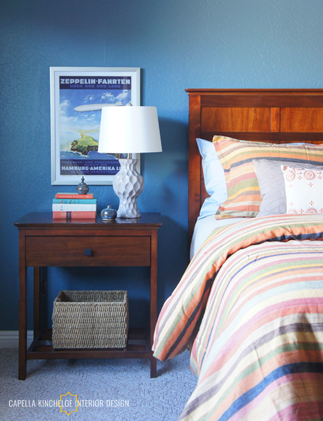 Colorful guest bedroom, travel poster art, blue walls