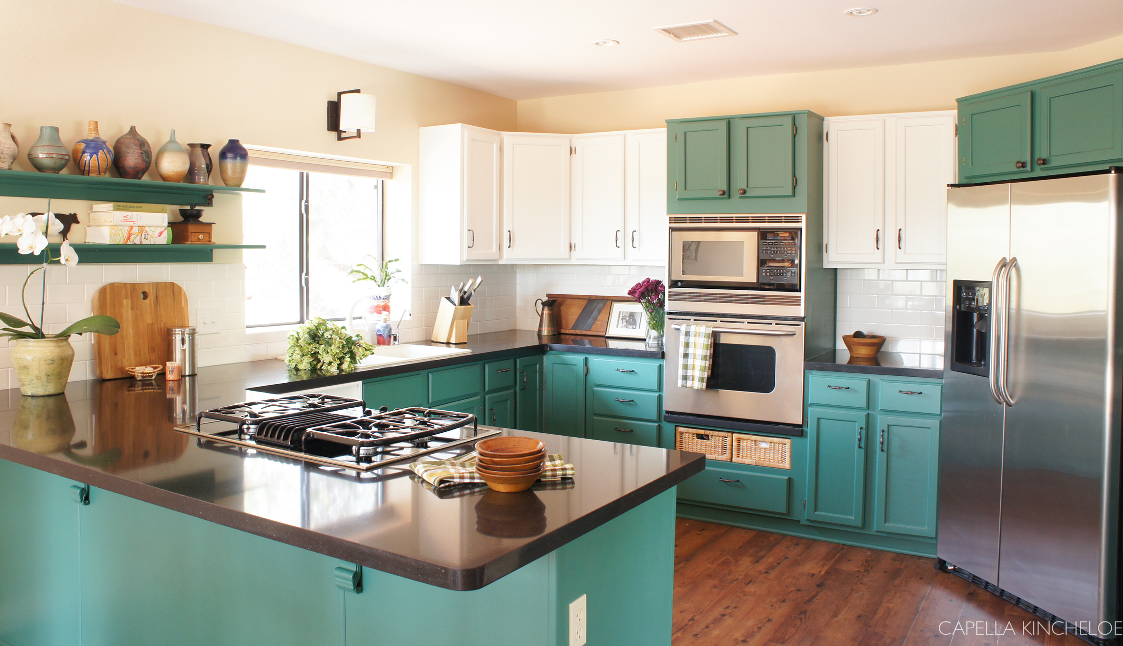 two tone cabinets, green kitchen cabinets, stainless steel appliances, black quartz counters open shelving