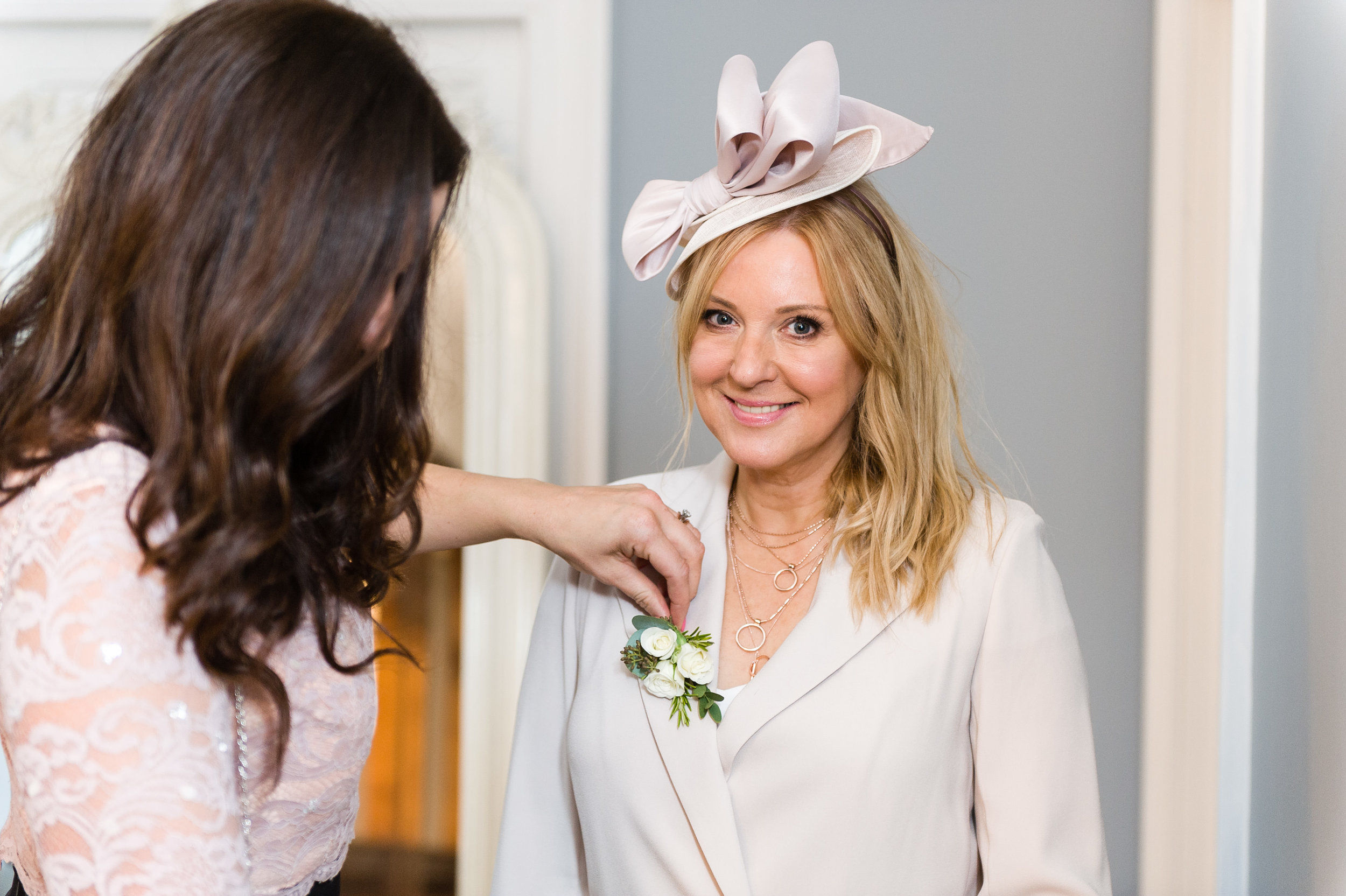 Kerry from Tineke pinning Mother of the Bride's corsage