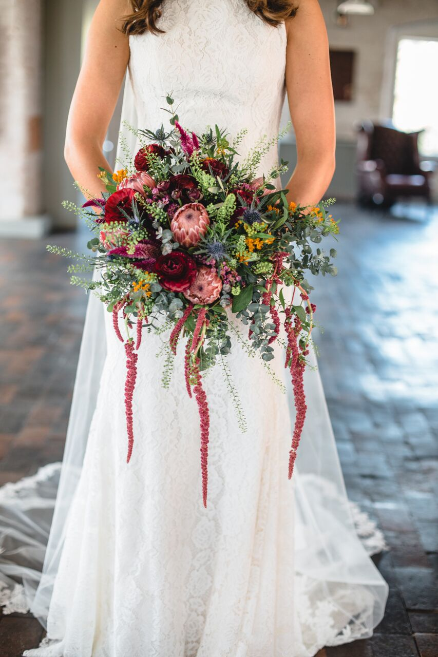 Red and blue vibrant bridal bouquet by Derbyshire florist Tineke. Featured at West Mill wedding venue.