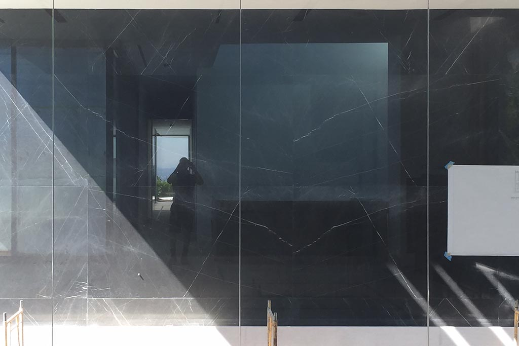 Existing black granite tiles on exterior walls before renovation
