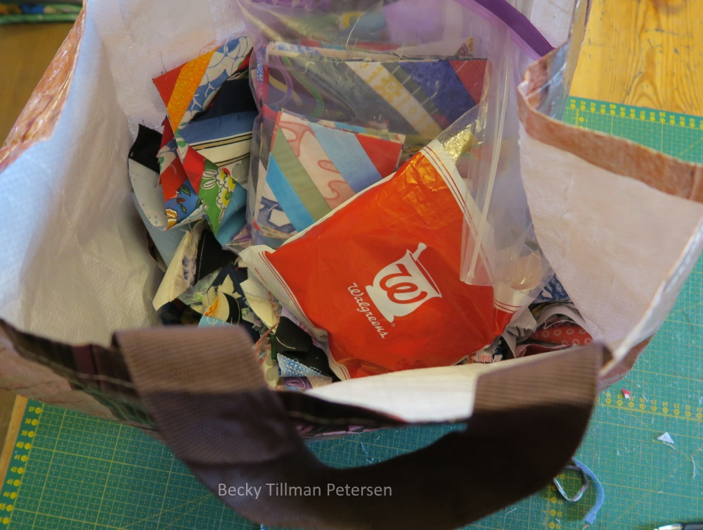"""In the bottom of this big bag are the various cut offs from the blocks I've gotten so far. The Walgreens prescription bag (from my dad's asthma medicine) holds some other smaller strips I've not pictured - since they are 2"""" wide by various lengths - not sure what to do wtih them, but something's brewing in my mind."""