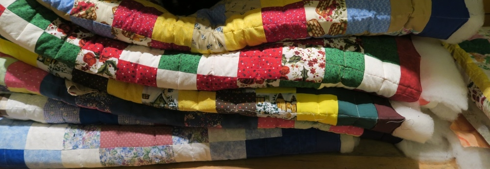 """I've learned to work in groups. This is a pile of 6 quilted quilts plus there is one to the right of these - barely showing in this picture. Once I get them bound and washed, I don't let the cats sit on them anymore. These are """"May's"""" quilts - but only 7. I am now out of batting and need to get to the store to get another bolt. Don't worry. I can get this batting locally - about 1/2 mile from my house and 50 meters of poly batting costs me less than most of you spend if you take your family w/kids out to eat once in a sit down restaurant in the USA."""