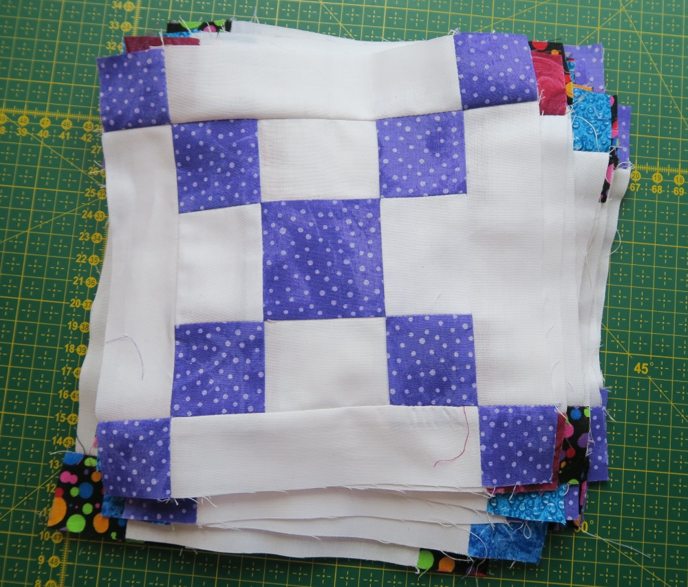 I made 22 of these blocks in various brights. I need 56, so in a couple more big sewing sessions, I should have them all done.