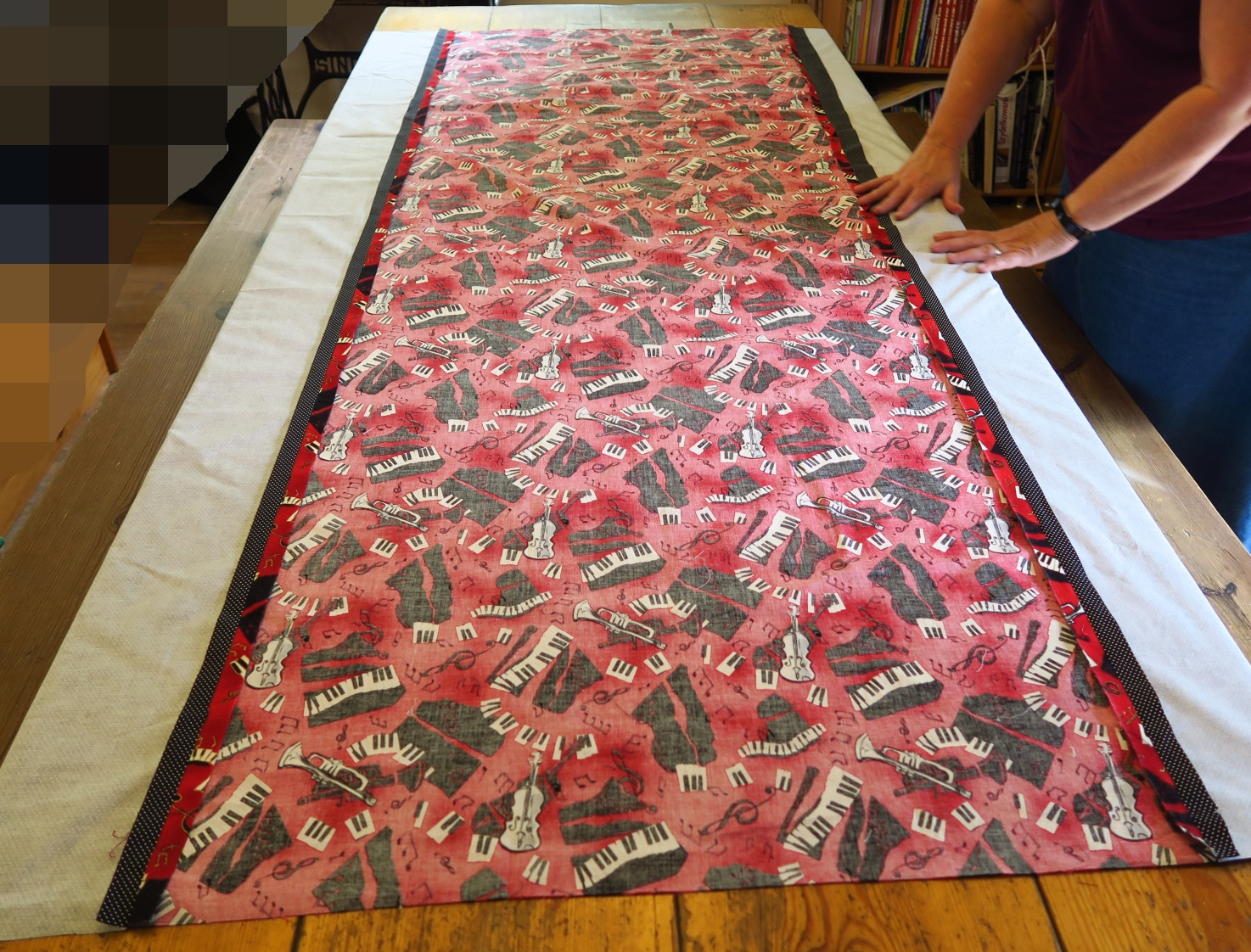She pieced a piece of red music fabric to two polka dot pieces (black) in order to make a backing the right size. She wanted to center the backing with the top, so we matched centers as we laid it out. I guess we'll check it at the end and see how accurate we got it (after washing).