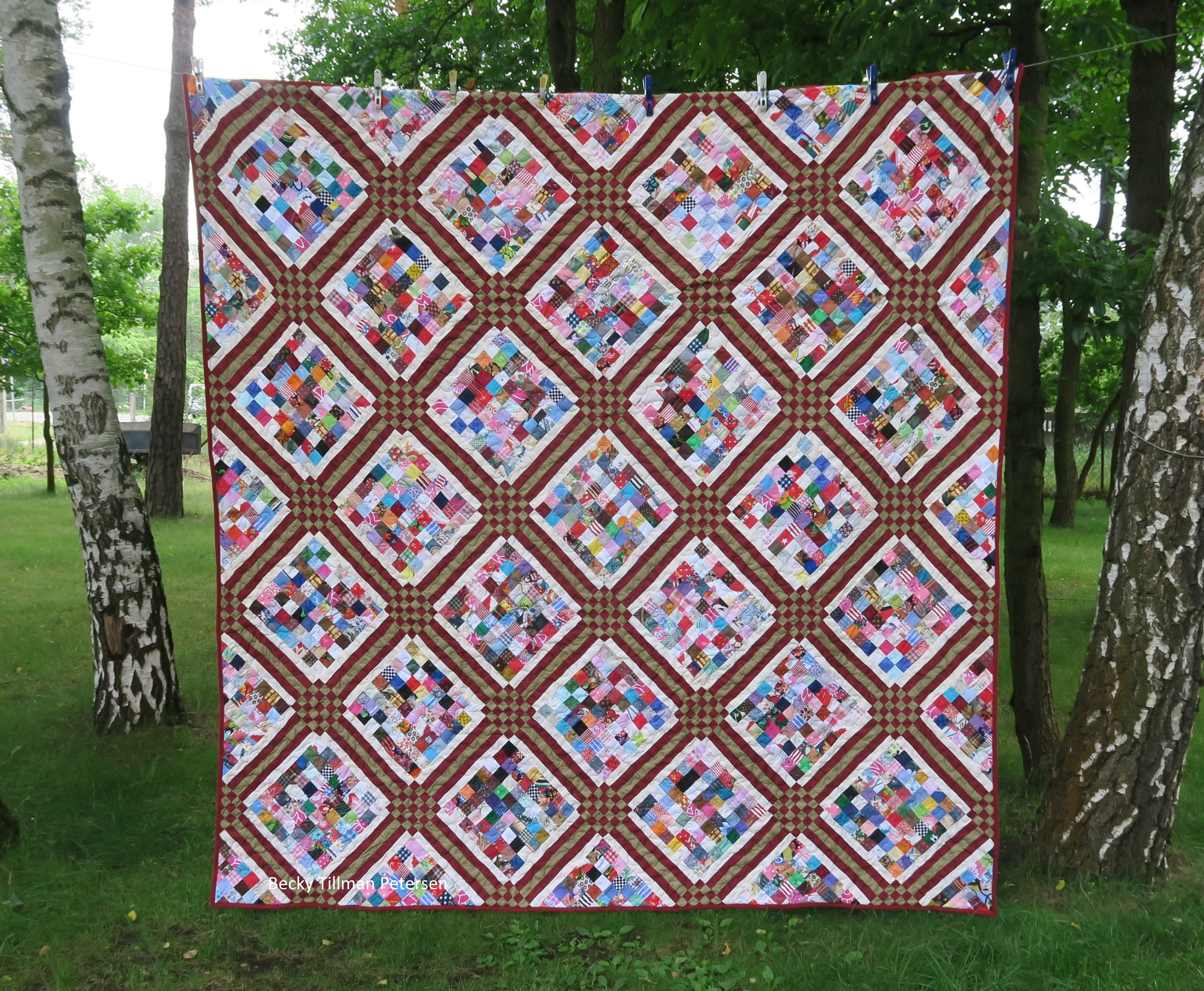 Picture of ice cube quilt, a quilt with burgandy and gold squares filled with leftover quit fabric squares