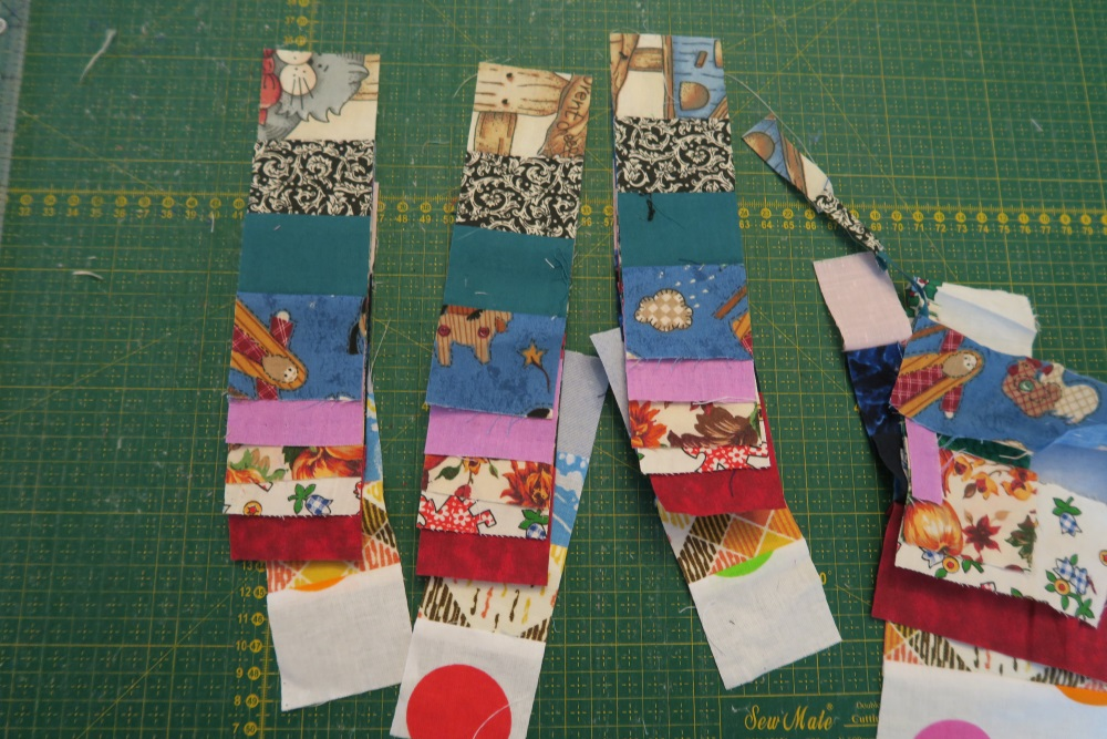 photo of three new two inche fabric pieces on top of green measuring pad, scrap fabric to the right of the photo